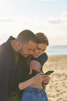 Junges paar, das auf sandstrand steht und smartphone betrachtet, mann zeigt finger auf handy