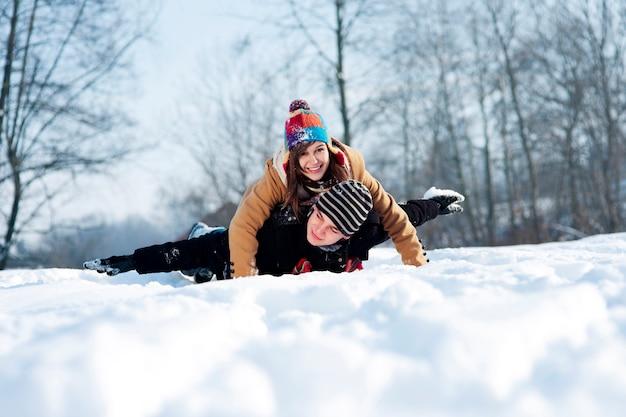 Junges paar, das auf schnee rodelt