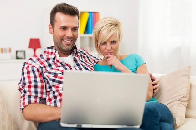 Junges paar, das auf sofa sitzt und laptop zu hause benutzt