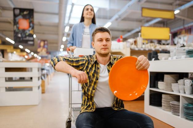 Junges paar, das auf wagen im haushaltswarenladen reitet. mann und frau kaufen haushaltswaren im markt, familie im küchengeschirrversorgungsgeschäft