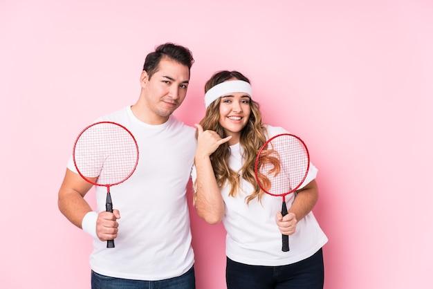 Junges paar, das badminton spielt, isoliert zeigt eine handy-anrufgeste mit den fingern.