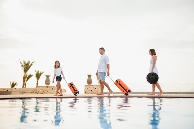 Junges paar, das bei der ankunft durch den pool ins hotel geht, zimmer sucht und koffer hält