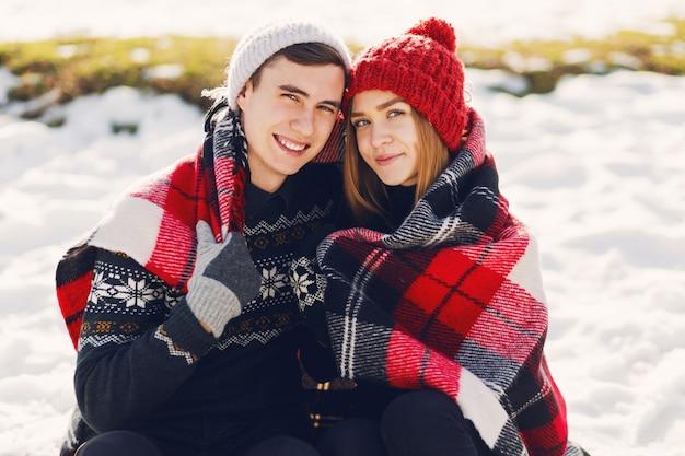 Junges paar, das decke auf einem schneebedeckten feld trägt