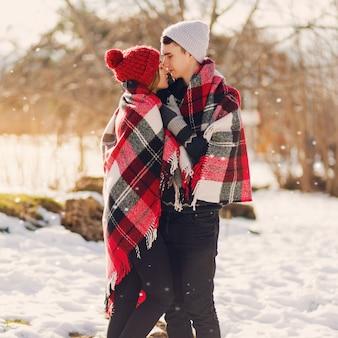 Junges paar, das deckenanzeige trägt, die auf einem schneebedeckten feld küsst