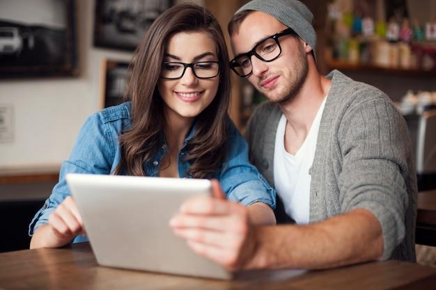 Junges paar, das drahtloses internet im restaurant genießt. d.