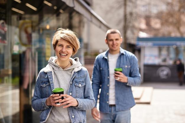 Junges paar, das duftenden kaffee trinkt, während es durch die stadt geht