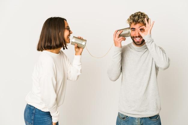 Junges paar, das durch eine blechdose spricht