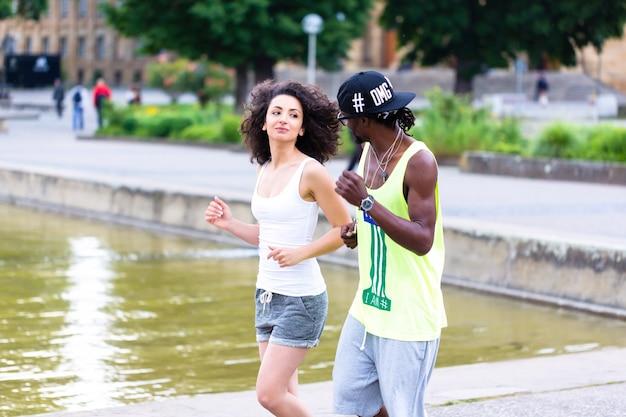 Junges paar, das durch stadtzentrum joggt