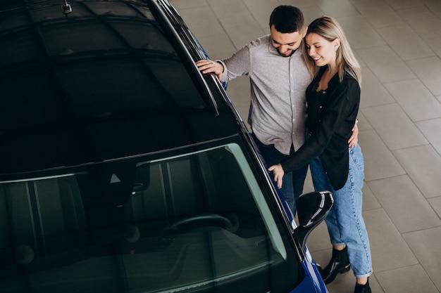Junges paar, das ein auto in einem autoausstellungsraum wählt
