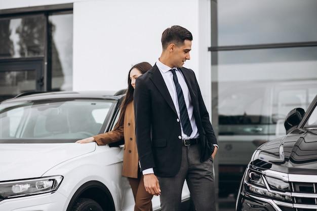 Junges paar, das ein auto in einem autohaus wählt