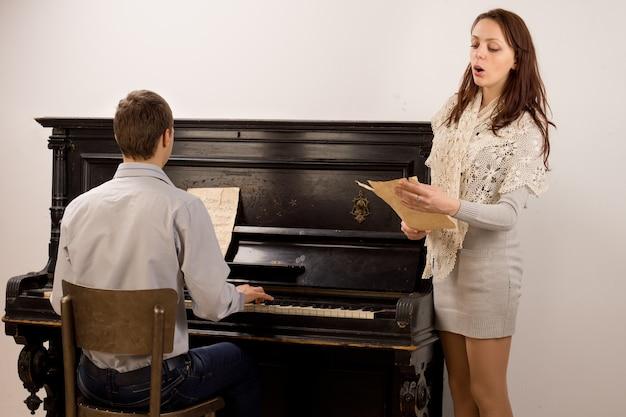 Junges paar, das ein klassisches duett mit einer attraktiven, stilvollen jungen frau gibt, die von einer musikpartitur singt, begleitet von einem jungen mann auf einem klavier
