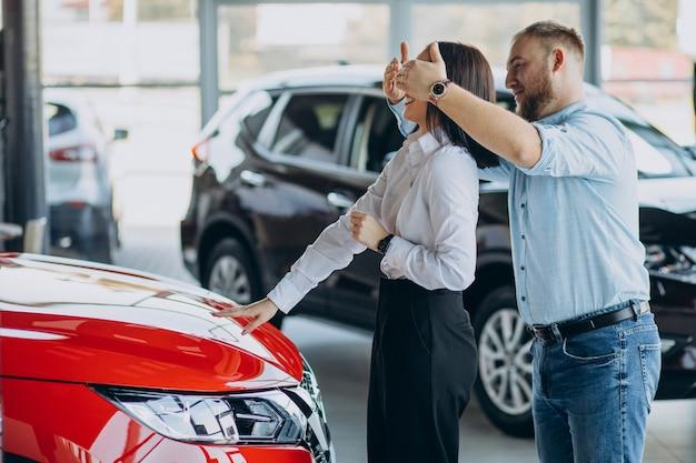 Junges paar, das ein neues auto kauft
