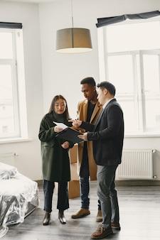 Junges paar, das ein neues haus kauft. asiatische frau und afrikanischer mann. unterschreiben von dokumenten im neuen zuhause.