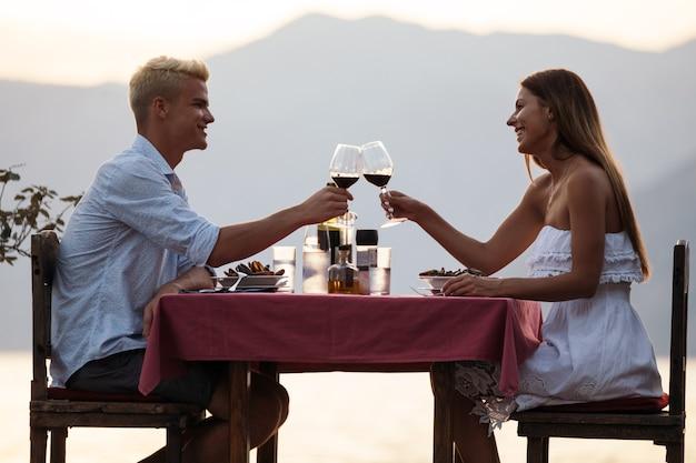 Junges paar, das ein romantisches abendessen bei sonnenuntergang am strand teilt