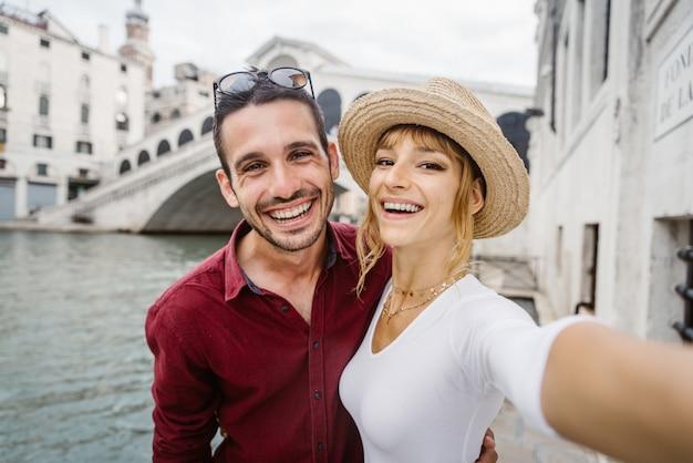 Junges paar, das ein selfie auf einer brücke nimmt