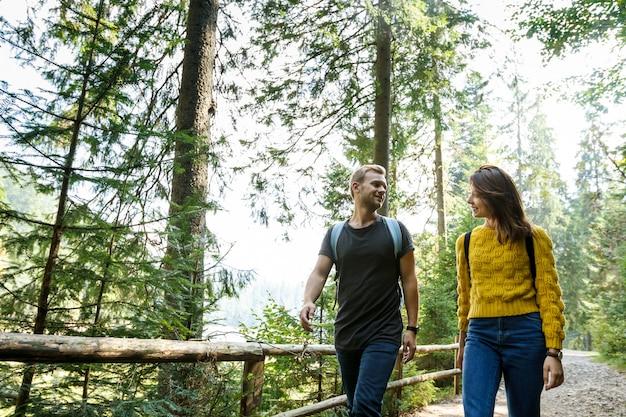 Junges paar, das einander betrachtet und im bergwald geht