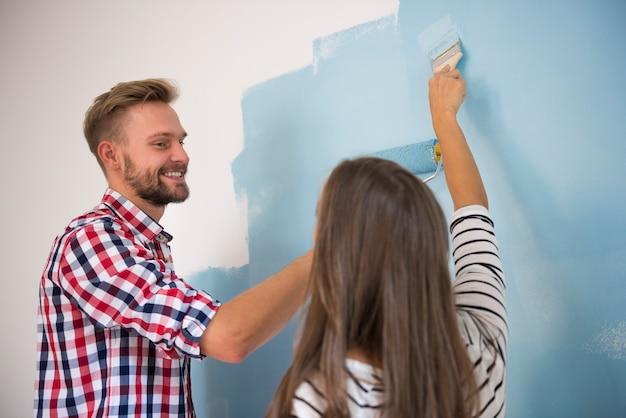 Junges paar, das eine blaue wand malt