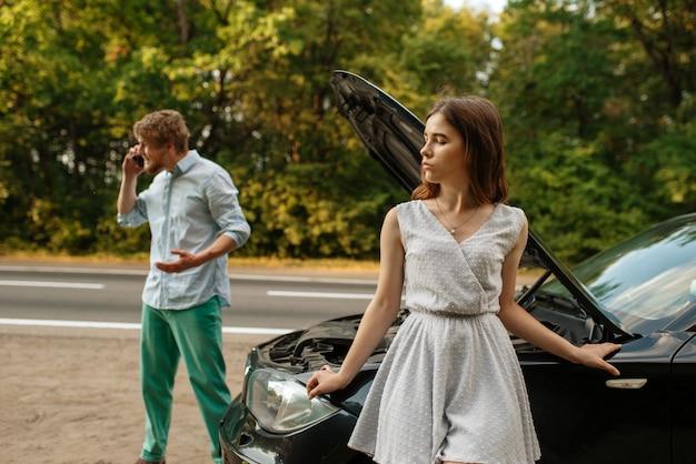 Junges paar, das einen abschleppwagen auf der straße anruft, autopanne. defektes auto oder notfallunfall mit fahrzeug, motorschaden auf der autobahn