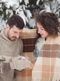 Junges paar, das einen heißen tee im winterpark hält