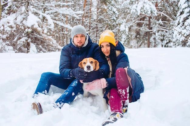 Junges paar, das einen hund in einem winterpark geht