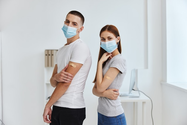 Junges paar, das einen pandemie-kovid mit einem klebepflaster-impfstoffpass hält