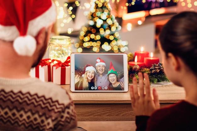 Junges paar, das einen weihnachtsvideoanruf mit ihrer familie hat. konzept der familie in quarantäne während weihnachten wegen des coronavirus