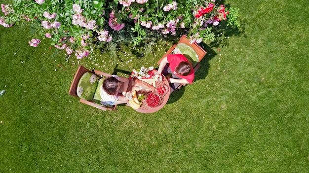Junges paar, das essen und getränke im schönen rosengarten am romantischen datum genießt, luftansicht von oben von mann und frau, die zusammen draußen im park essen und trinken