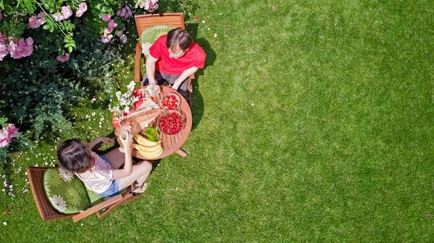 Junges paar, das essen und getränke im schönen rosengarten an einem romantischen datum genießt