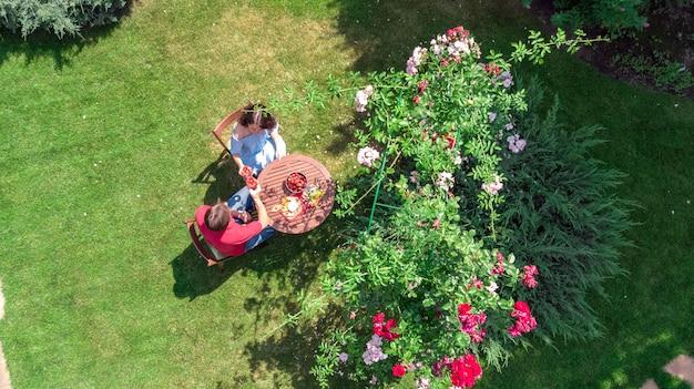 Junges paar, das essen und wein im schönen rosengarten am romantischen datum genießt, luftansicht von oben von mann und frau, die zusammen draußen im park essen und trinken