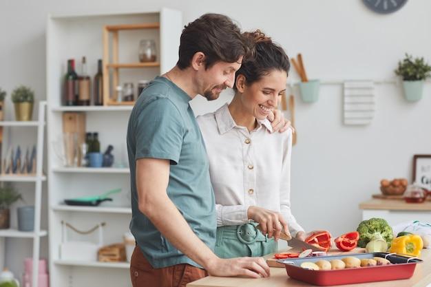 Junges paar, das essen zusammen in der küche zubereitet, bereitet gericht aus gemüse vor