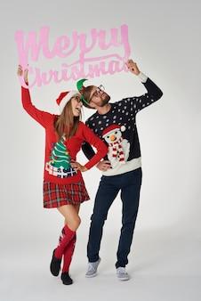 Junges paar, das fahne mit weihnachtsgrüßen hält