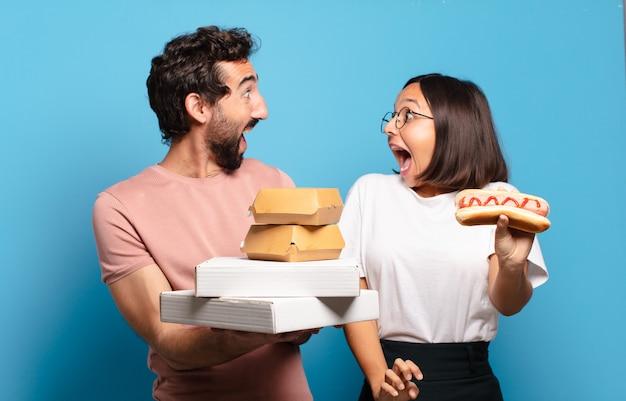 Junges paar, das fast food mit nach hause nimmt.