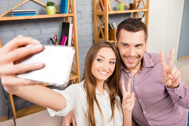 Junges paar, das foto auf smartphone macht und mit zwei fingern gestikuliert
