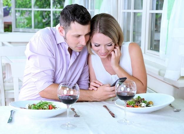 Junges paar, das foto mit handy im restaurant nimmt