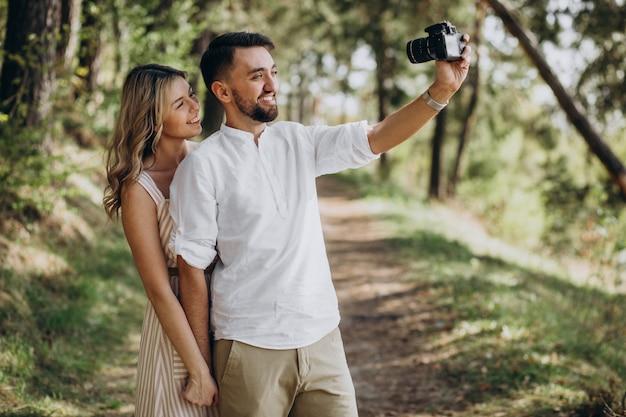 Junges paar, das fotos im wald macht