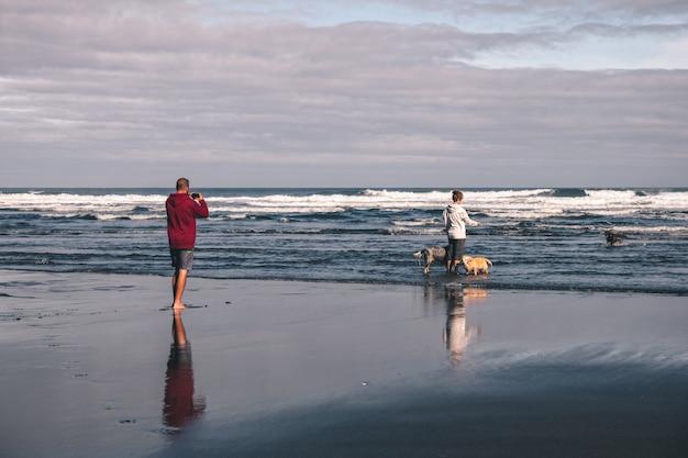 Junges paar, das fotos macht und mit ihren hunden am strand im frühling in asturien, spanien spielt