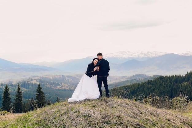 Junges paar, das für hochzeitsfotoshooting in den bergen aufwirft