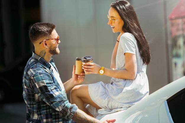 Junges paar, das für urlaubsreise auf dem auto am sonnigen tag vorbereitet. frau und mann, die kaffee trinken und bereit sind, zum meer oder zum ozean zu gehen.