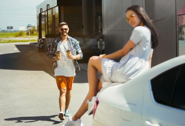 Junges paar, das für urlaubsreise auf dem auto am sonnigen tag vorbereitet