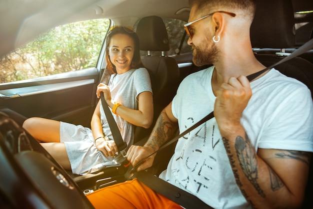 Junges paar, das für urlaubsreise auf dem auto am sonnigen tag vorbereitet.