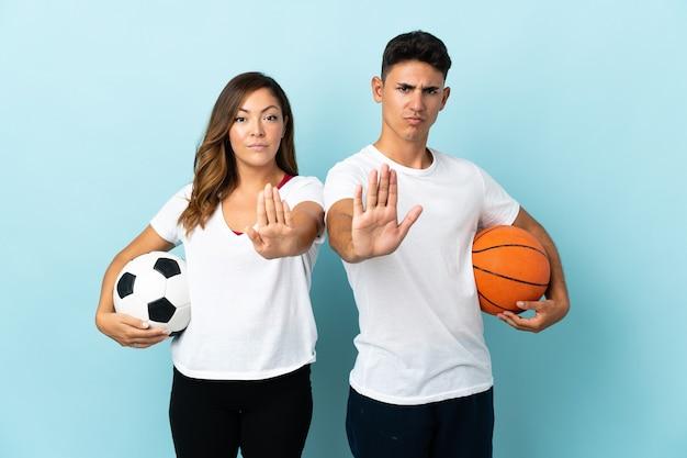 Junges paar, das fußball und basketball auf blau spielt und stop-geste macht, die eine situation leugnet, die falsch denkt