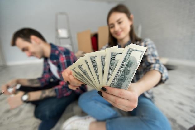 Junges paar, das geld zählt, während es in einer neuen wohnung auf dem boden sitzt?