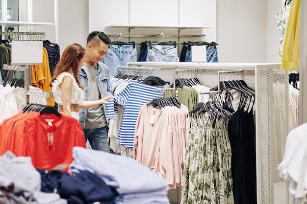 Junges paar, das gestreiftes hemd im einkaufszentrum kauft