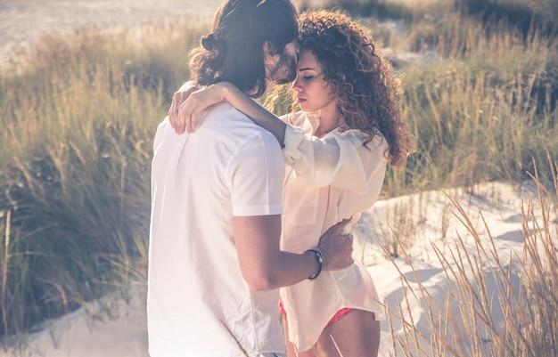 Junges paar, das glückliche und liebesstimmung am strand teilt