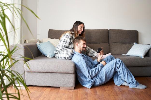 Junges paar, das handy zusammen betrachtet, gekleidet in pyjamas zu hause. sie sind glücklich und lachen im urlaub und genießen es, zusammen zu sein.