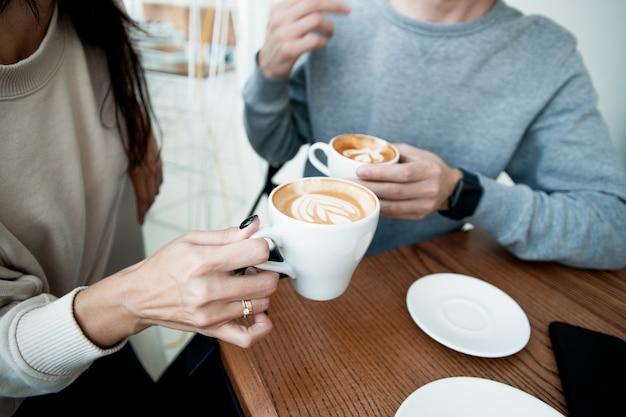 Junges paar, das heiße getränke trinkt. nahaufnahme von frau und mann, die im café sitzen und warme tassen kaffee auf dem tisch halten. mann und frau verbringen zusammen ein wochenende im gemütlichen kaffeehaus. romantisches date-konzept.