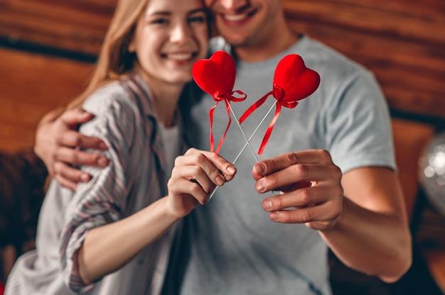 Junges paar, das herzen in den händen hält, sich umarmt und spaß hat, während es den valentinstag feiert.