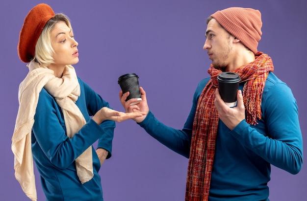 Junges paar, das hut mit schal am valentinstag trägt, beeindruckte mädchen, die mit der hand auf einen mann mit einer tasse kaffee auf blauem hintergrund zeigen