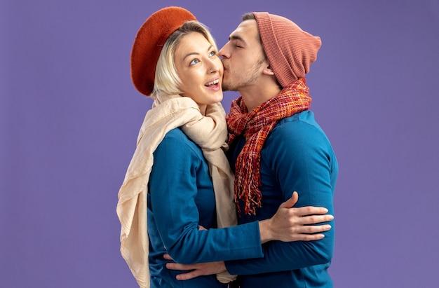 Junges paar, das hut mit schal am valentinstag trägt, freut sich über einen kerl, der mädchen auf die wange küsst, isoliert auf blauem hintergrund