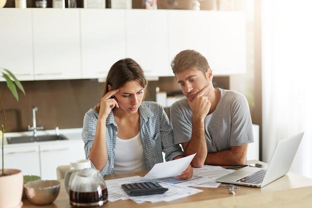 Junges paar, das ihr familienbudget überprüft